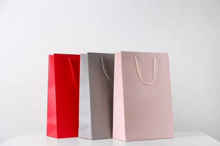 Paper shopping bags on white table against light background