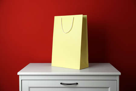 Paper shopping bag on white chest of drawers against red background