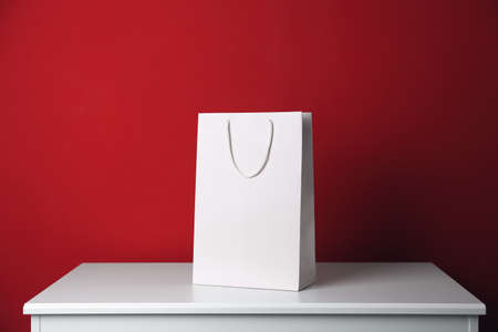 Paper shopping bag on white table against red background