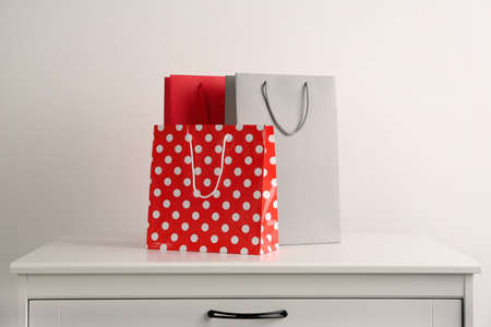 Paper shopping bags on white chest of drawers against light background 写真素材