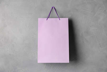 Paper shopping bag hanging on gray wall 写真素材