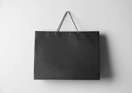 Paper shopping bag hanging on white wall 写真素材