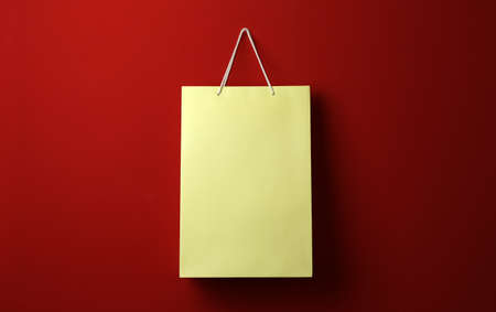 Paper shopping bag hanging on red background 写真素材