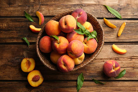 Fresh sweet peaches in wicker basket on wooden table, flat lay