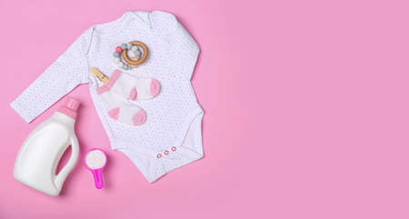 Flat lay composition with bottle of detergent and children's clothes on pink background. Space for text