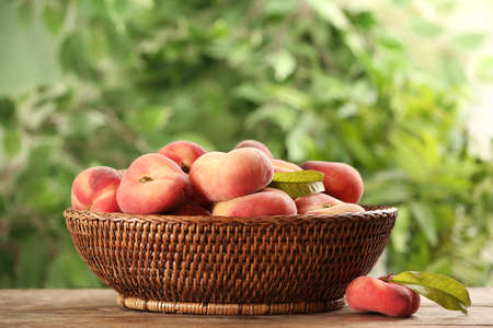 Fresh ripe donut peaches on wooden table against blurred green background