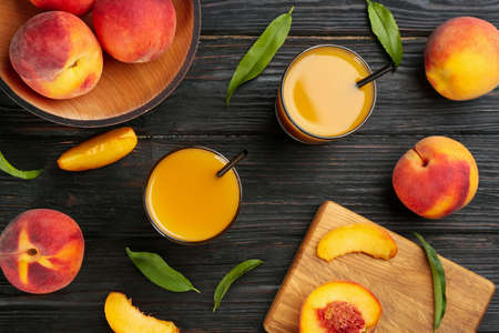 Natural peach juice and fresh fruits on black wooden table, flat lay
