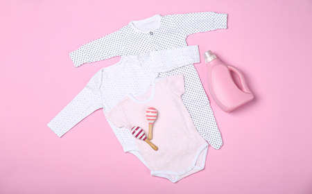 Flat lay composition with bottle of detergent and children's clothes on pink background 版權商用圖片