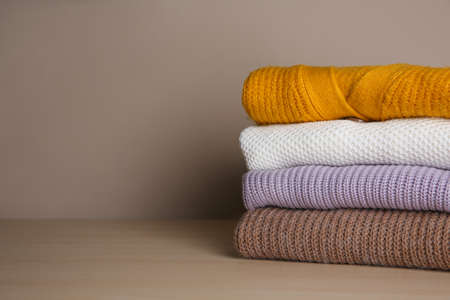 Stack of folded knitted sweaters on wooden table. Space for text