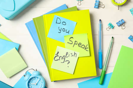 Question DO YOU SPEAK ENGLISH? and stationery on white wooden background, flat lay