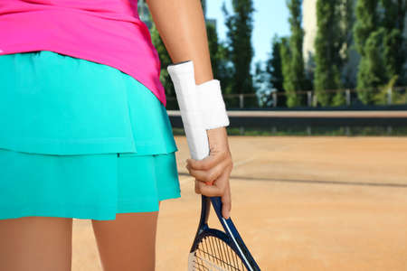 Sportswoman with racket at tennis court on sunny day, closeup Banque d'images