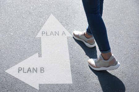 Choosing between Plan A and Plan B. Woman near pointers on road, closeup view