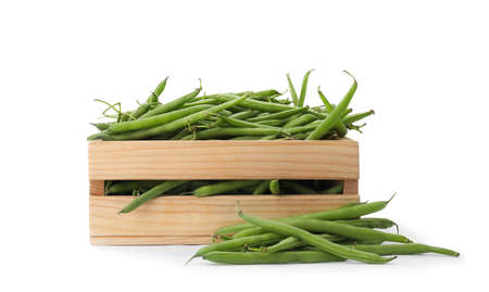Fresh green beans in wooden crate on white background