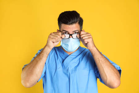 Doctor wiping foggy glasses caused by wearing medical mask on yellow background
