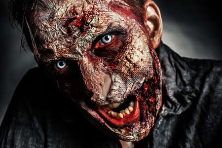 Scary zombie on dark background, closeup. Halloween monster Imagens