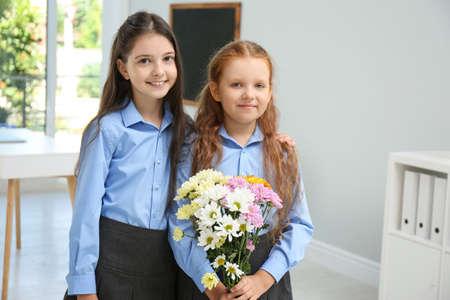 Happy schoolgirls with bouquet in classroom. Teacher's day