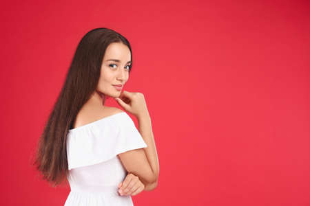 Young woman wearing stylish white dress on red background. Space for text