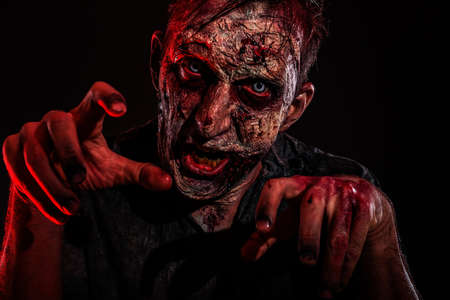 Scary zombie on dark background. Halloween monster Imagens