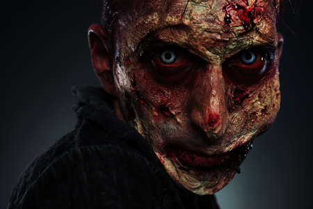 Scary zombie on dark background, closeup. Halloween monster