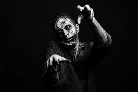 Scary zombie on dark background, black and white effect. Halloween monster