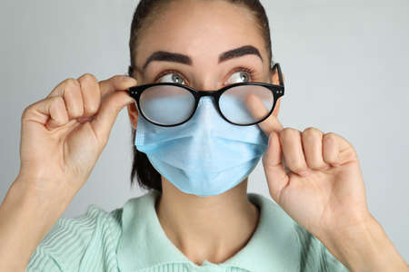 Woman wiping foggy glasses caused by wearing medical mask on light background, closeup Banque d'images