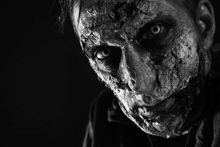 Scary zombie on dark background, black and white effect. Halloween monster Фото со стока