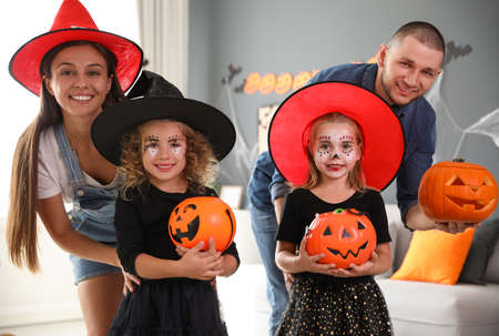 Happy family with Halloween candy buckets and pumpkin head jack lantern at home Stockfoto