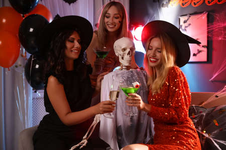 Women with cocktails near skeleton at Halloween party