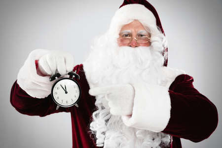 Santa Claus holding alarm clock on light gray background. Christmas countdown Stock Photo