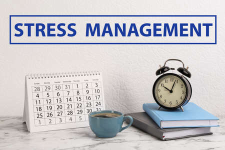 Text Stress Management over table with calendar, alarm clock, notebooks and cup of coffee Stock Photo