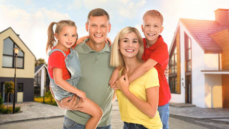 Happy family standing in front of their house on sunny day Standard-Bild