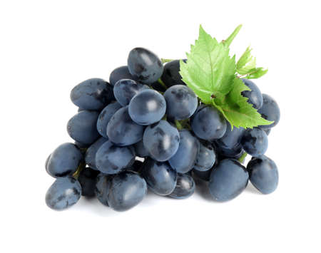 Bunch of dark blue grapes with green leaves isolated on white Foto de archivo
