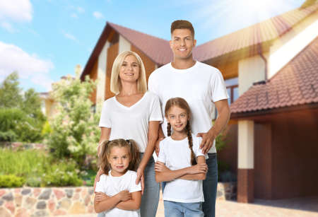 Happy family standing in front of their house on sunny day Archivio Fotografico