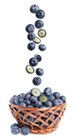 Fresh whole blueberries falling into wicker basket on white background Zdjęcie Seryjne
