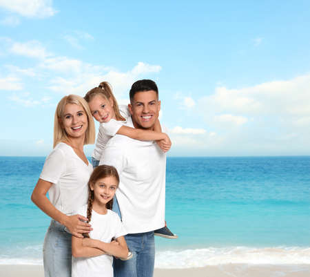 Happy family on sandy beach near sea. Summer vacation