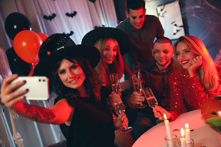 Group of friends taking selfie at Halloween party indoors