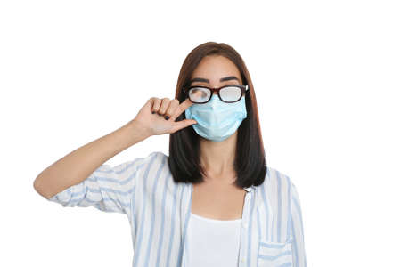 Young woman wiping foggy glasses caused by wearing disposable mask on white background. Protective measure during pandemic