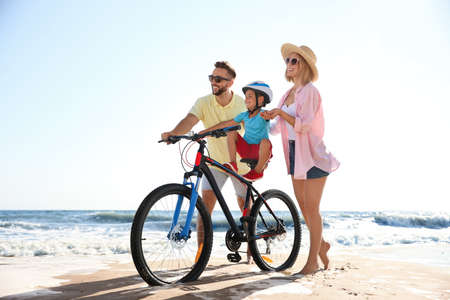 Happy parents teaching son to ride bicycle on sandy beach near sea