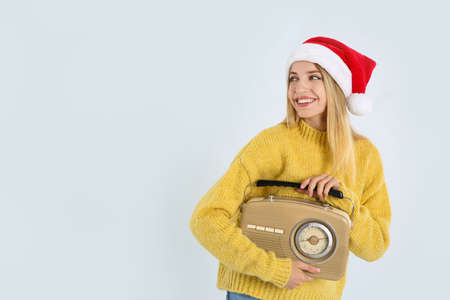 Happy woman with vintage radio on white background, space for text. Christmas music
