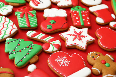 Different Christmas gingerbread cookies on red background, closeup Foto de archivo