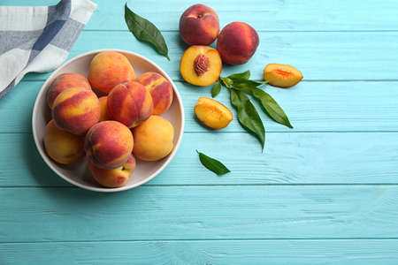 Fresh sweet peaches on turquoise wooden table, flat lay. Space for text Standard-Bild