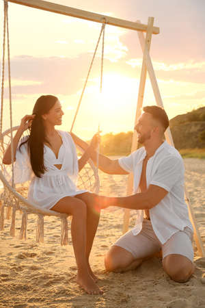 Happy young couple on beach at sunset