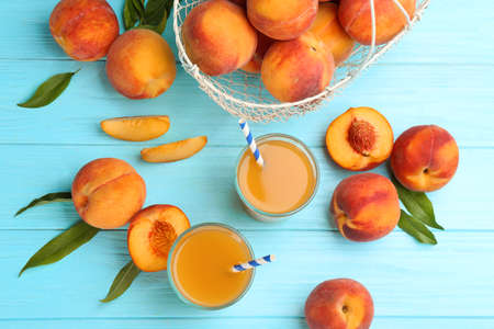 Natural peach juice and fresh fruits on light blue wooden table, flat lay