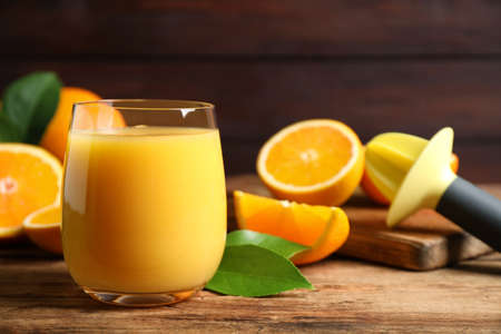 Glass of orange juice and fresh fruits on wooden table, closeup