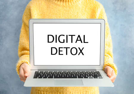 Woman holding laptop with phrase DIGITAL DETOX on light blue background, closeup