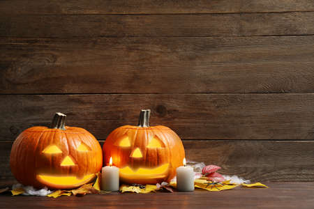 Pumpkin jack o'lanterns, autumn leaves and candles on wooden table, space for text. Halloween decor