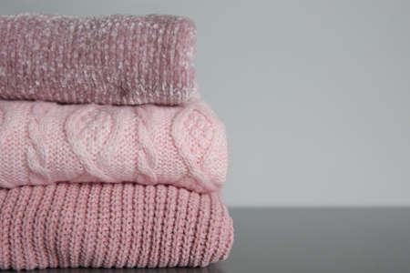 Stack of folded knitted sweaters on gray table, closeup. Space for text