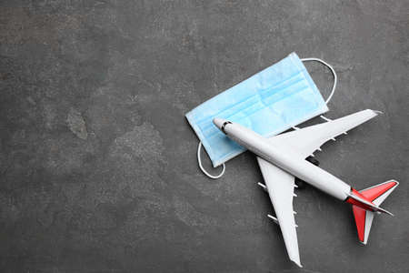 Toy airplane and protective mask on gray background, flat lay with space for text. Traveling during coronavirus pandemic
