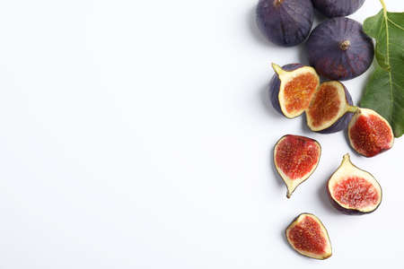 Delicious ripe figs with green leaf on white background, top view
