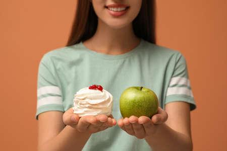 Woman choosing between apple and cake on orange background, closeup